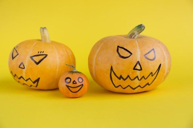 黄色の背景の概念の親と子の恐ろしい邪悪な顔を持つハロウィーンのカボチャの家族は...