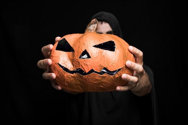 Halloween pumpkin in hands of young man