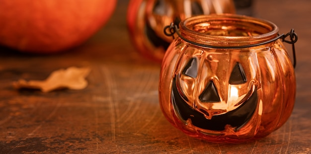 Halloween pumpkin head jack glass lantern. halloween decoration on wooden table background, selective focus copy space for text - image