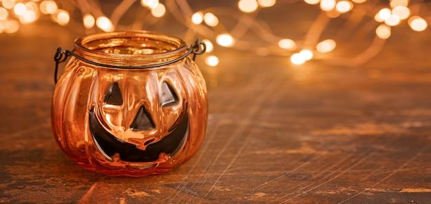 Halloween pumpkin head jack glass lantern. halloween decoration on wooden table background, selective focus - image
