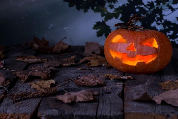 Halloween pumpkin head jack o lantern glowing in a mystic forest at night.