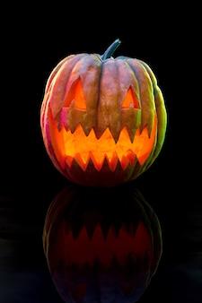 恐ろしい邪悪な顔を持つハロウィーンのカボチャの頭のジャック・オー・ランタン。季節のイルミネーションデコレーション。怖い、カラフルなネオンの明るい背景と暗い背景に見えます。休日。ブラックフライデー、セール。恐怖の夜。