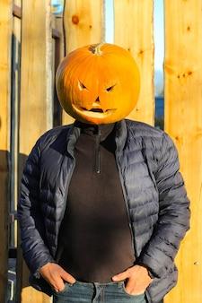 Человек головы тыквы хеллоуина в костюме фонаря джека осенью.