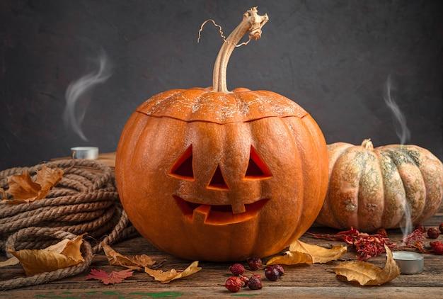 ハロウィーンのカボチャジャックは、葉と吹き消されたキャンドルで暗い背景に向かいます