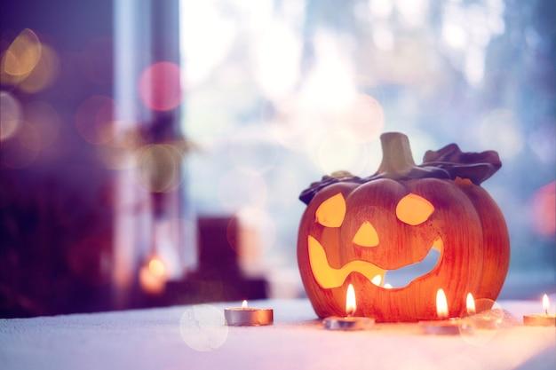 ろうそくとハロウィーンのカボチャランプは、ハロウィーンの屋内装飾の家のシンボルでテーブルに火をつけます