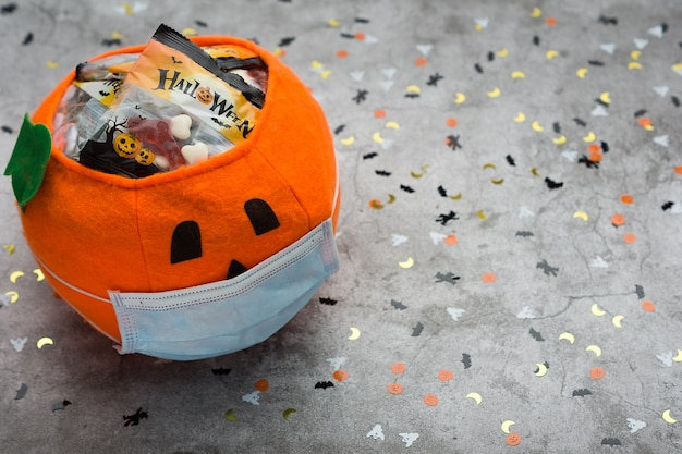 Halloween pumpkin made of fabric with mask filled with jelly beans, decorated with halloween motifs