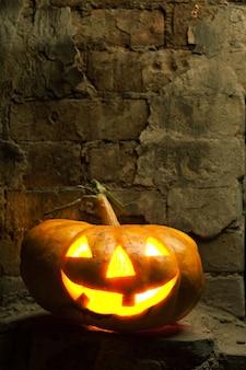 Halloween pumpkin in night on old brick wall