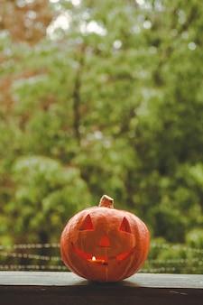Тыква хэллоуина на уютном подоконнике с красным пледом. целая тыква и бенгальский огонь на открытом воздухе. счастливого хэллоуина! осень уютная. дождь снаружи.