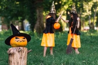Halloween pumpkinon background of girls in witch costumes