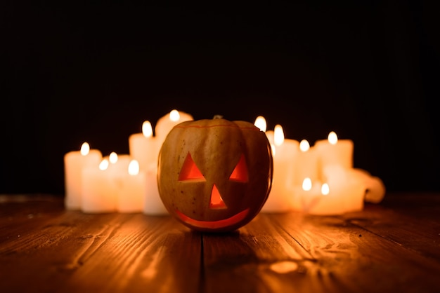 Тыква хэллоуина на фоне свечей и черном фоне.