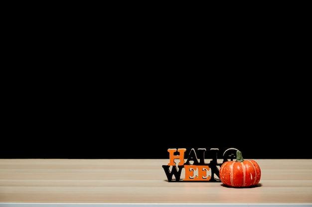 木製のテーブルの黒い壁の暗い背景にハロウィーンのカボチャ