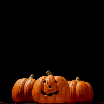 Тыква хэллоуина на деревянном столе перед жуткой темнотой
