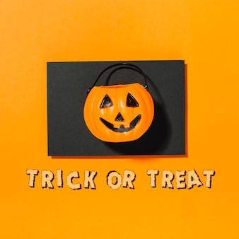 Zucca di halloween su pezzo di carta nera con iscrizione dolcetto o scherzetto