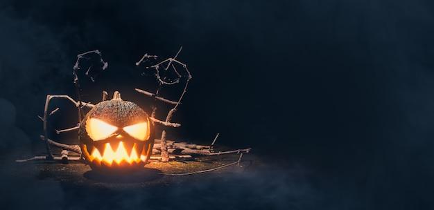 Тыква хэллоуина, улыбаясь, видя зубы с дымом на темном и страшном фоне. тыква на хеллоуин резная