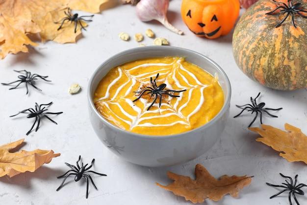 회색 그릇에 크림 거미줄과 테이블에 거미가 있는 할로윈 호박 수프. 확대