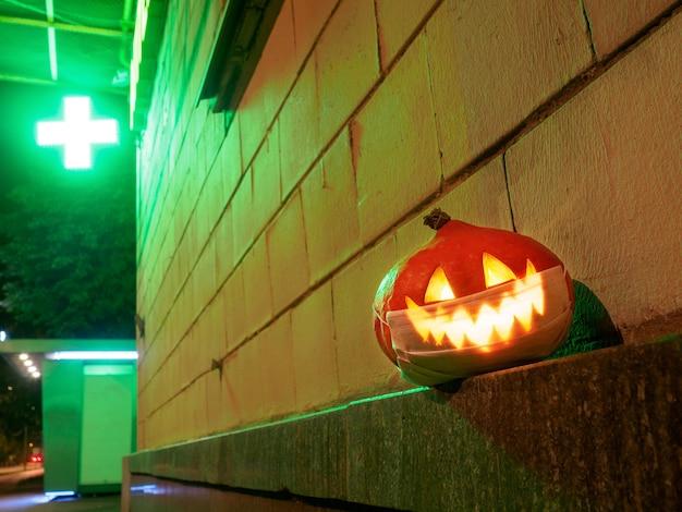 Хэллоуинская тыква с защитной маской на лице на фоне аптечного креста