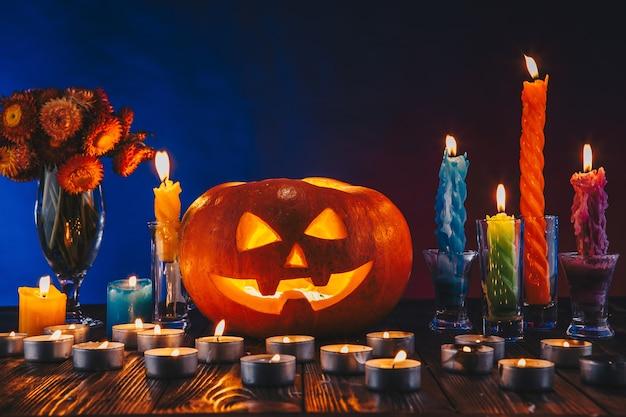 Хэллоуин тыква с большим количеством свечей и цветов при темном освещении. кошелек или жизнь на синем и красном фоне