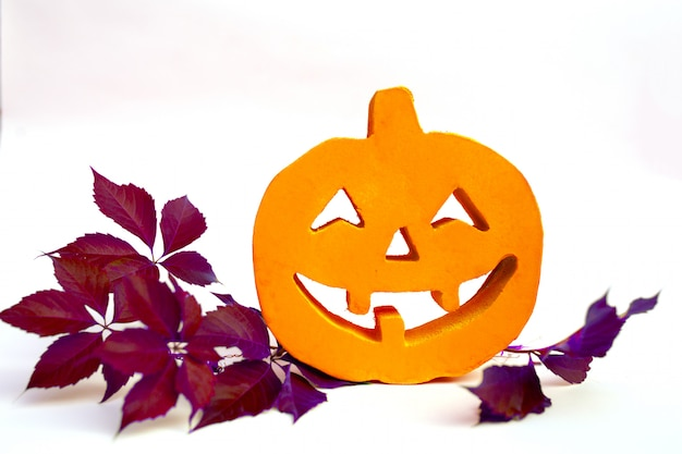 Halloween pumpkin with autumn leaves and white