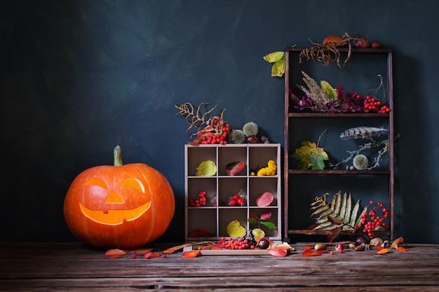 暗い背景に秋の自然の装飾とハロウィーンカボチャ