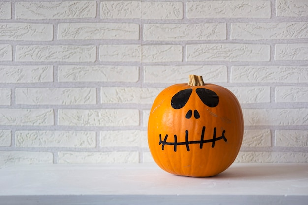 Halloween pumpkin with black eyes and mouth, with white brick wall.