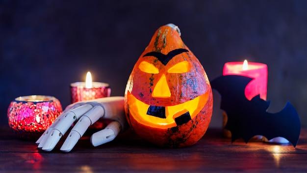 暗い背景に燃えるろうそくとハロウィーンのカボチャ。ハロウィーンのカボチャの笑顔と木の手で怖い目。ハロウィーンのコンセプト