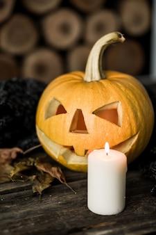 Тыква хеллоуина с свечой кофе на древесине.