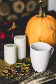 Тыква хеллоуина с кофейной чашкой на древесине.