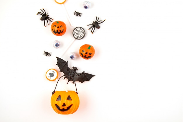 Halloween pumpkin with halloween party objects, bats, spiders and treats