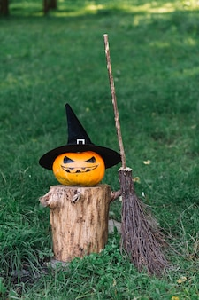 Halloween pumpkin with hat on stump near broomstick