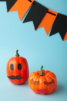 Halloween pumpkin with make up on blue. minimal holiday season concept background. man and woman. vertical photo