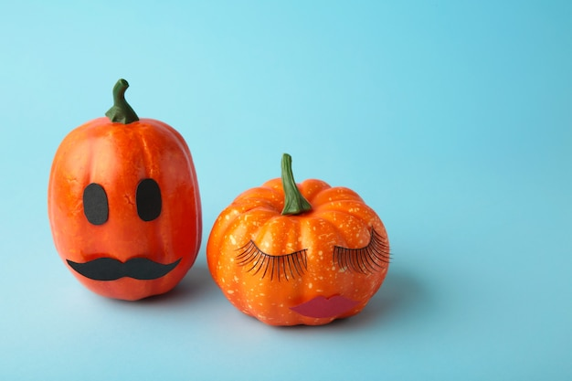 Halloween pumpkin with make up on blue. minimal holiday season concept background. man and woman