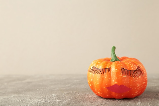 Halloween pumpkin with make up. minimal holiday season concept background. top view