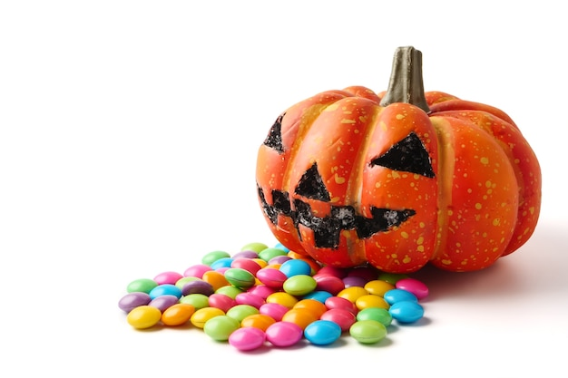 Halloween pumpkin with pile of candy on a white background.