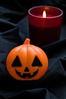 暗い背景に赤いろうそくとハロウィンのカボチャ。ジャック・オ・ランタン。