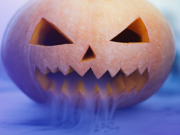 Halloween pumpkin with scary face on dark