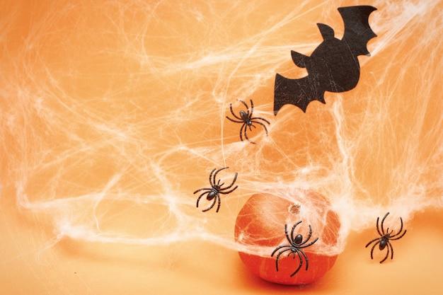 오렌지 배경에 거미줄 박쥐와 검은 거미와 할로윈 호박