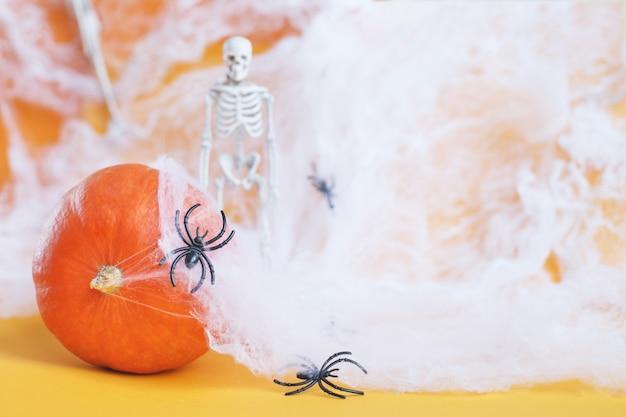 주황색 배경에 거미줄 골격과 검은 거미가 있는 할로윈 호박
