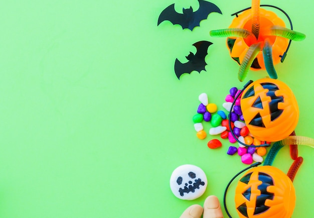 Halloween pumpkin with sweets candies on green background