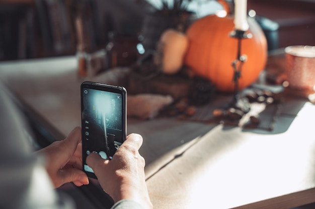 Halloween pumpkin and woman taking a picture with her phone in a table with decoration