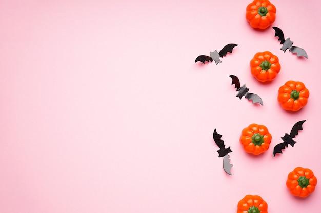ピンクの背景、テキスト用のスペース、フラットレイのハロウィーンのカボチャとコウモリ。