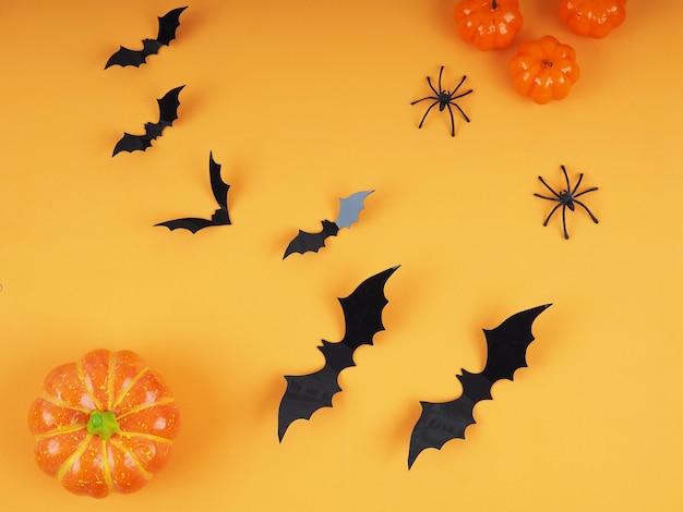 オレンジ色の背景を持つハロウィーンのカボチャとコウモリ-ハロウィーンのフラットレイ構成。