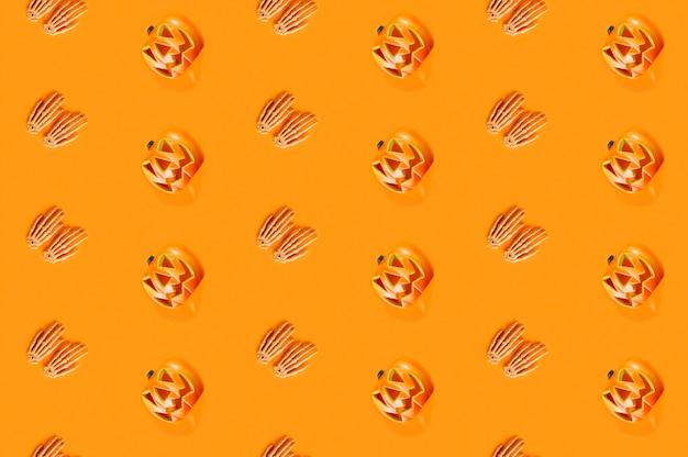 Хэллоуинские тыквы и скелетные руки лежат ровными линиями
