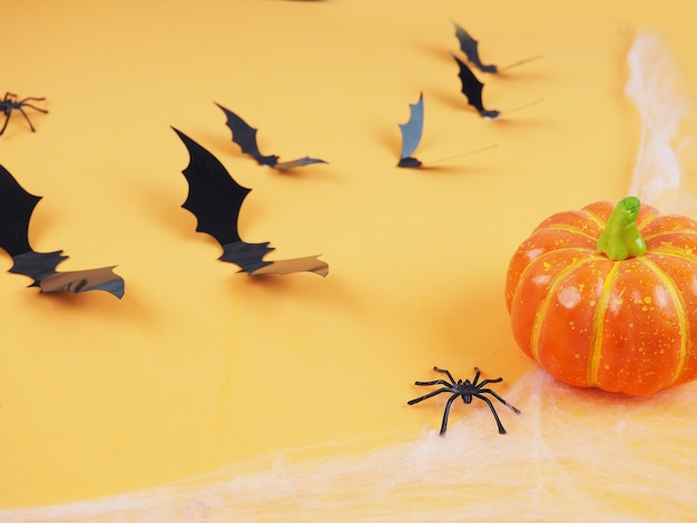 Halloween pumpkins and bats with orange background- halloween flat lay composition.