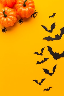 Halloween pumpkins and bats with orange background