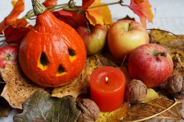 Halloween pumpkins and candle on wooden, autumn composition with leaves and apples