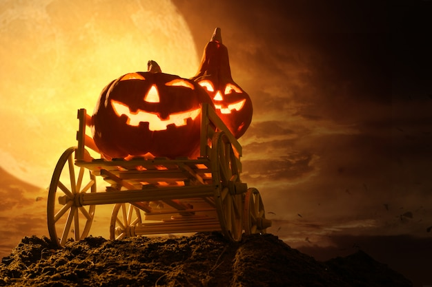 Halloween pumpkins on farm wagon at spooky in night of full moon