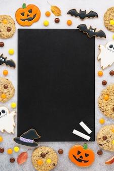 Halloween pumpkins, ghosts cookies and candy around chalkboard