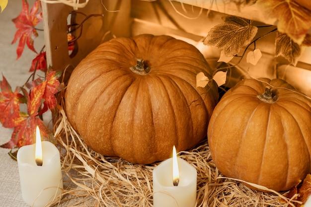 キャンドル、ストロー、秋の紅葉と木箱でハロウィンのカボチャ