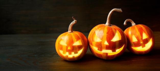 Тыквы хеллоуина на темном деревянном столе. фон хэллоуина.