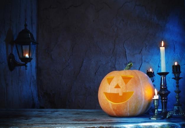 暗い背景に木製のテーブルにハロウィンのカボチャ